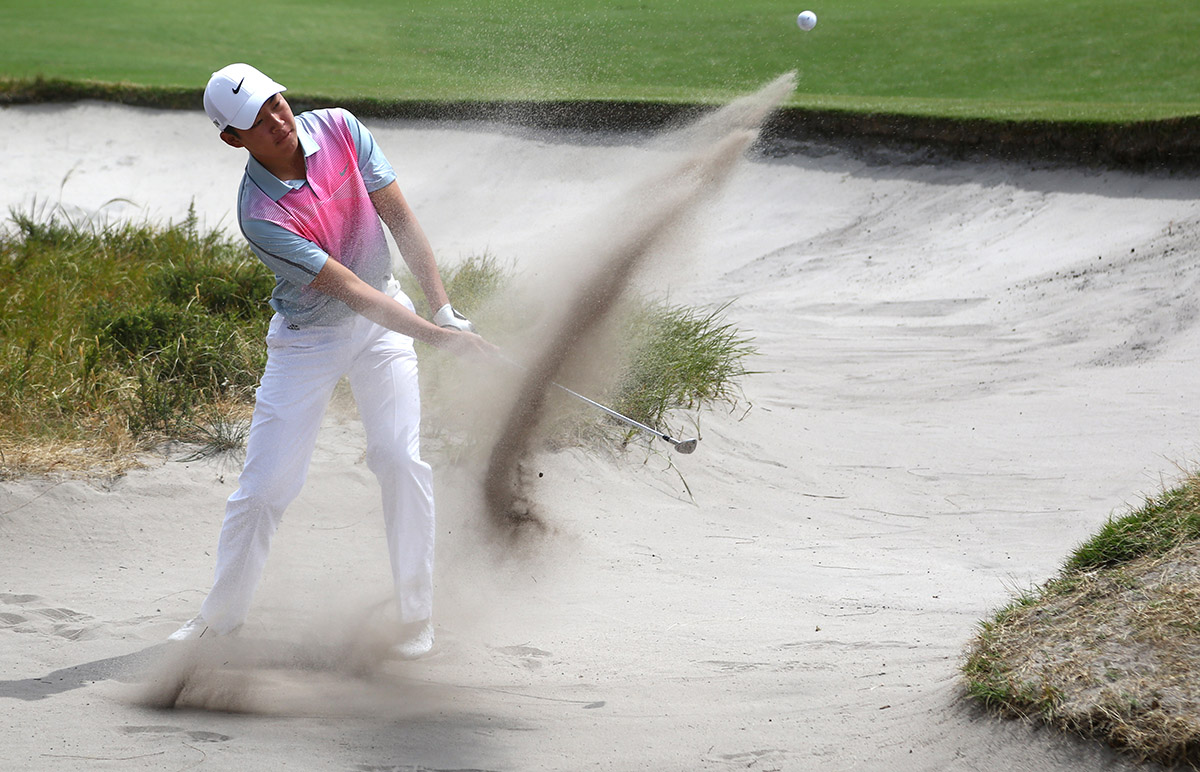 Melbourne, Australia: Jin Cheng  of China plays from the sand during round 3 of the Asia-Pacific Amateur Championship at the Royal Melbourne Golf Club). October 25 2014, (photo by Ian Knight/AAC)