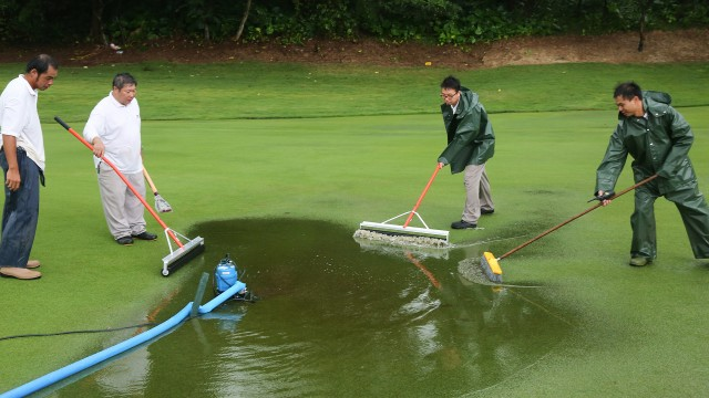 Hong Kong: Officials clears the waterlogged from the green when the storm hit the course, during the Final Round of the 2015 Asia-Pacific Amateur Championship at the Clearwater Bay Golf & Country Club in Hong Kong on October 04, 2015. (Photo by Daniel Cheng/AAC)