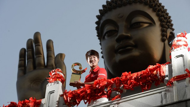 LONGKOU CITY, China - Lee Chang-woo of Korea pictured with the winner's trophy at the Nanshan Buddha after the final round on Sunday October 27 at the Asia -Pacific Amateur Championship at Nanshan International Golf Club, Garden Course. Lee secured an invitation to the 2014 Masters Tournament and a place in International Final Qualifying for The Open Championship. Picture by Paul Lakatos/AAC.